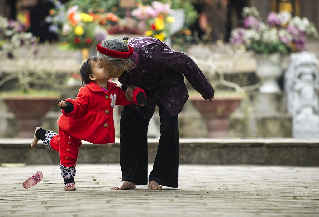 Lovely image of young girlg kissing grandmother in Vietnam