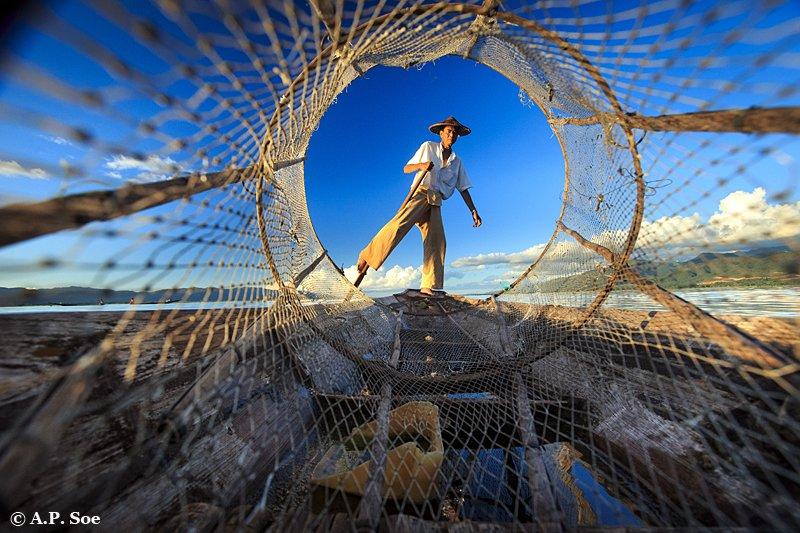 Inle Lake shot of Intha fishermen through his net on Burma photo tour
