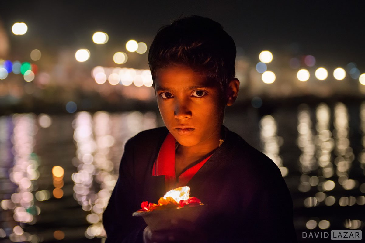 Boy at nightwith candle on the Ganges River at Varanasi.