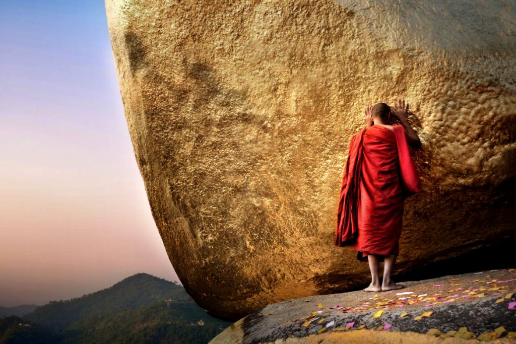 Monk prays at Golden Rock, Myanmar photo