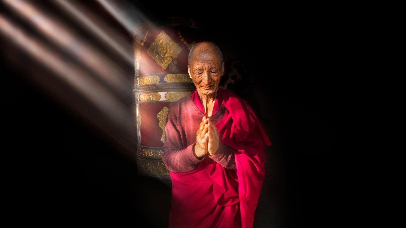 Tibetan monk with light beams taken on a Ladakh photography trip