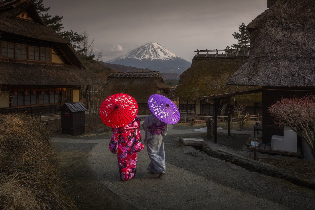 Mt. Fuji snowcapped with traditional Japanese attire in a nearby village