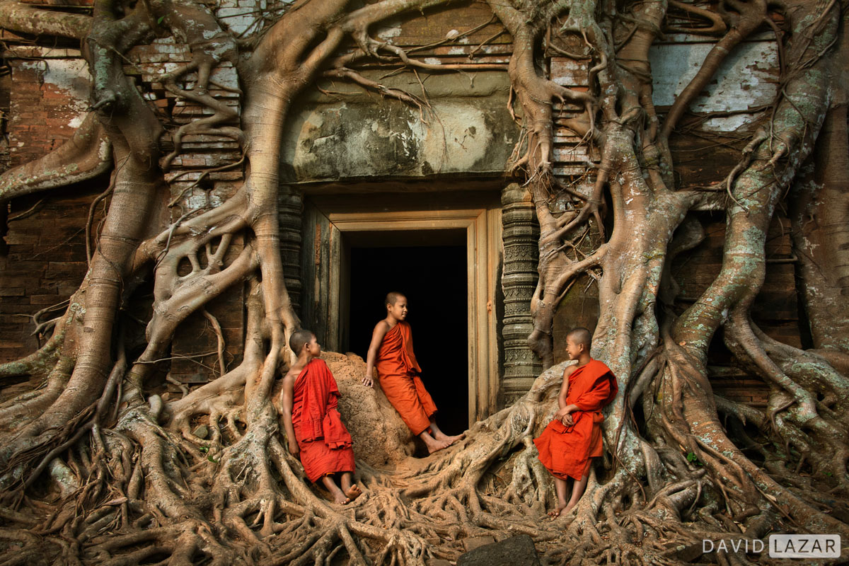 Off-the-beaten-path-image-of-Khmer-temple-with-giant-tree-roots-and-young-monks